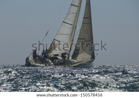 Crew on board yacht in competitive team sailing event - stock photo