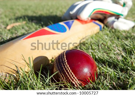 Cricket ball, bat and gloves on the field. - stock photo
