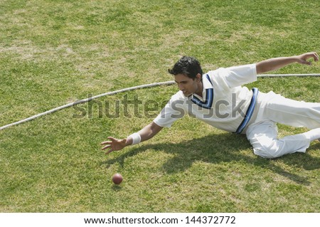 Cricket fielder diving to stop a ball near boundary line - stock photo