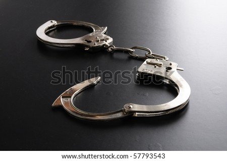 crime and law concept with police handcuffs on desk - stock photo