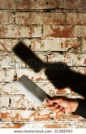 Crime concept. Hand holding an axe shaped knife in front of brick wall with harsh shadow. - stock photo