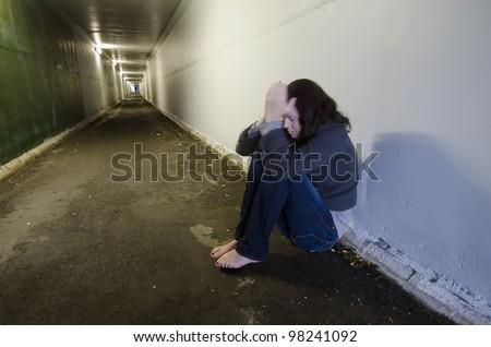 Crime scene concept photo of rape victim. A sad woman sits on the floor of a dark tunnel. - stock photo
