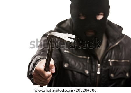 Crime scene - criminal thief or burglar man in balaclava or mask covering face holding crowbar in hand for break opening home door lock - stock photo