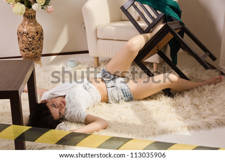 Crime scene imitation. Lifeless woman lying on the floor - stock photo
