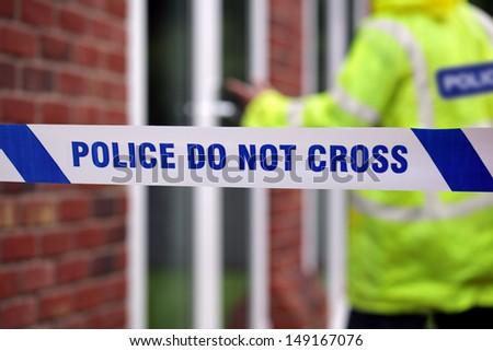 Crime scene investigation police do not cross boundary tape investigating policeman - stock photo