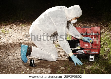 Crime scene investigation - technician and suitcase - stock photo