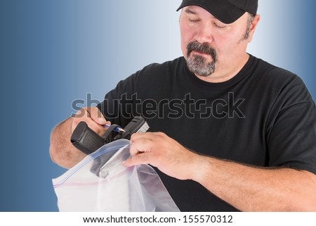 Crime scene investigator founds a gun, he is placing the gun in to a evidence bag seriously without touching for further analysis, isolated on light blue background - stock photo