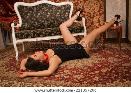 Crime scene simulation. Lifeless woman in a luxurious lingerie lying on the floor