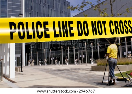 Crime scene tape with a camerman in the near background and a SWAT team in the far background. - stock photo
