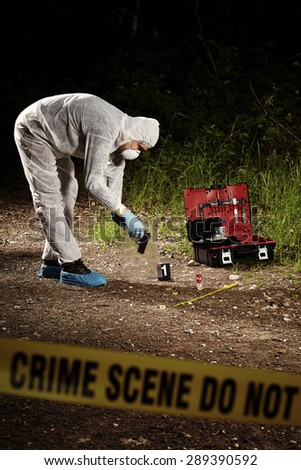 Crime scene technician collecting pistol and cartridges on forest way - stock photo