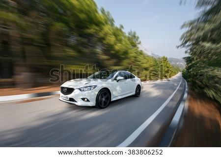 Crimea, Russia - September 20, 2015: White car Mazda speed driving on asphalt road at daytime - stock photo