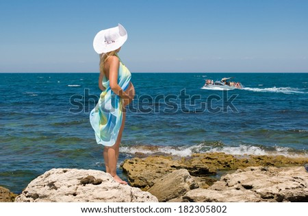 Crimea, the sea, rocks and a pregnant woman. Clear Skies.