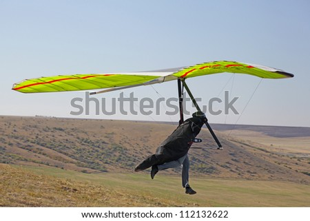 CRIMEA, UKRAINE - SEPTEMBER 4: Competitor of hang gliding competitions takes part in the Klementieva mountain on September 4, 2012 in Crimea, Ukraine - stock photo