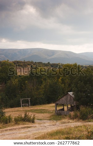 Crimean landscape. Panorama including mountains, wooden arbour, swing and cloudy sky. Stormy weather
