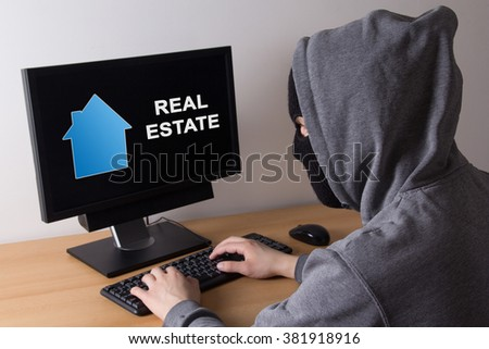 criminal and burglary concept - thief in mask searching info about real estate in internet - stock photo
