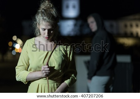 Criminal observing young woman walking alone at night - stock photo