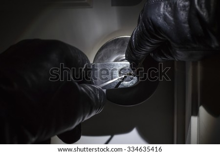 Criminal Picking Lock with Black Leather Gloves at Night - stock photo
