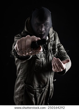 Criminal pointing gun at camera - stock photo