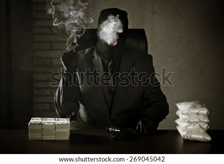 Criminal sitting in a warehouse with stack of money and bags full of drugs on table - stock photo