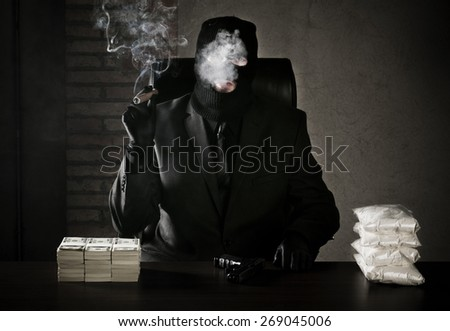Criminal sitting in his office in a warehouse with stack of money and bags full of drugs on table - stock photo
