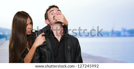 Criminal With A Gun Threatening Young Woman at a port - stock photo