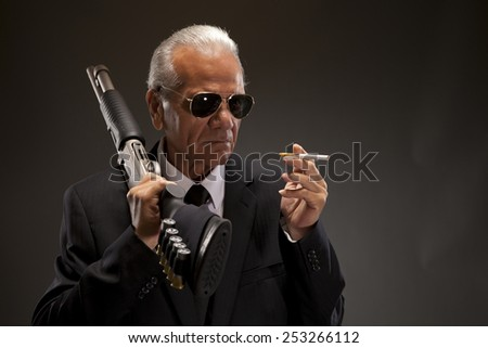 Criminal with shotgun and smoking cigarette against dark background - stock photo