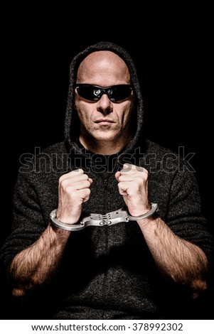Criminal with sunglasses and hood trapped in handcuffs - stock photo