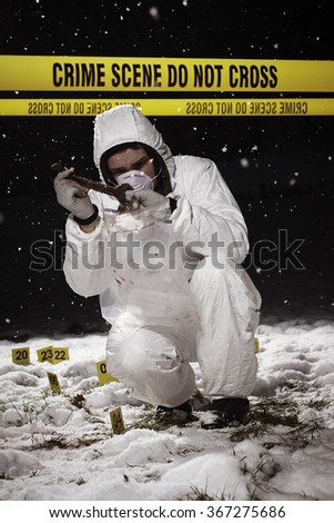 Criminologist technician at work on place of crime in winter time - stock photo