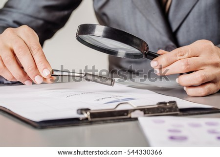 Criminology expert through a magnifying glass looking at a bullet