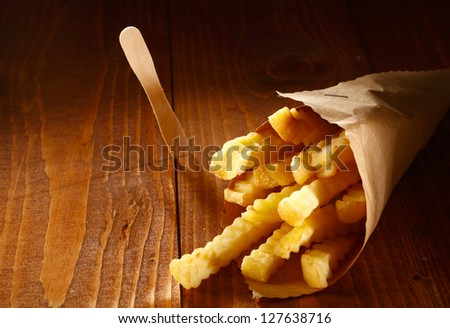 Crinkle cut golden french fries served as a takeaway in a roll of brown paper lying on a wooden table with copyspace