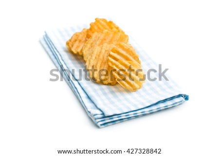 Crinkle cut potato chips isolated on white background. Tasty spicy potato chips on checkered napkin. - stock photo