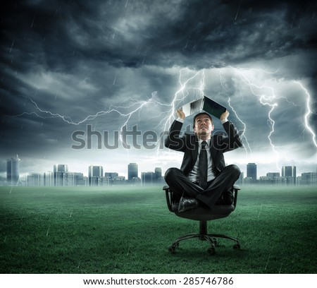 crisis - businessman is repaired by storm with computer  - stock photo
