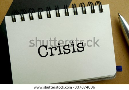 Crisis memo written on a notebook with pen - stock photo