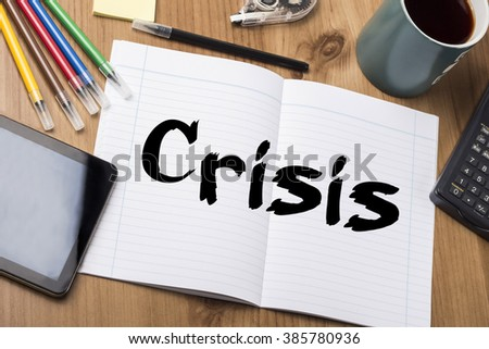 Crisis - Note Pad With Text On Wooden Table - with office  tools - stock photo