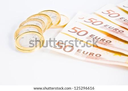 crisis of eurozone, detail of some euro coins on 50-euro banknotes on white background - stock photo
