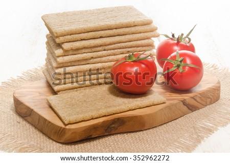 crisp bread with fresh tomato on a wooden board - stock photo