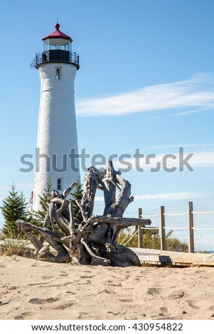 Crisp Point Lighthouse on the shores of Lake Superior in the Upper Peninsula of Michigan. A driftwood tree stump lays in the foreground - stock photo