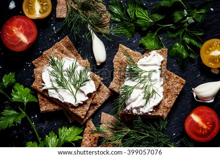 Crisp rye bread with soft curd cheese with herbs and spices on a dark background, food background, top view - stock photo