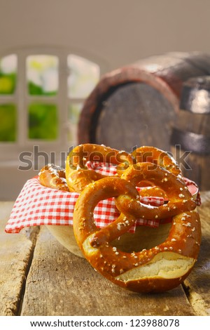 Crisp salty golden-brown pretzels served as a savoury snack in a pub or restaurant with an old wine barrel visible behind