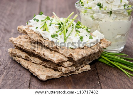Crispbread, Cream Chesse and Chives on wooden background - stock photo