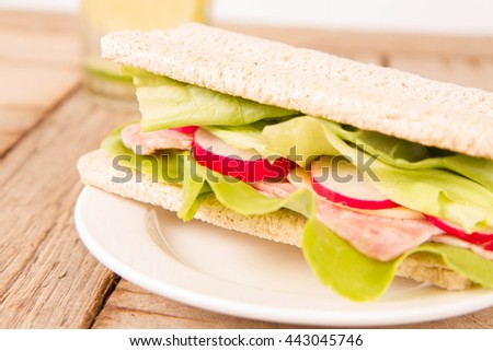Crispbread sandwich with headcheese, cheese, radish and lettuce