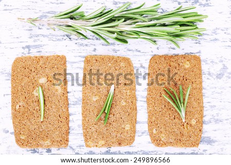 Crispbread with sprigs of rosemary on color wooden background - stock photo