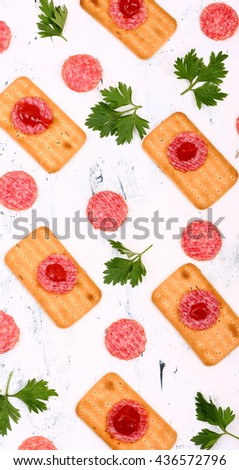 Crispy bread with salami and fresh parsley on white wooden table. - stock photo