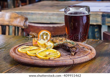 Crispy chicken leg with apples, oranges and beer - stock photo