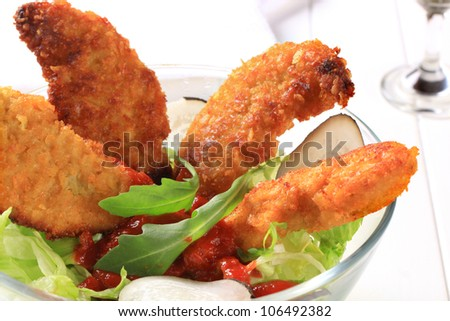 Crispy chicken tenders with tomato dipping sauce   - stock photo