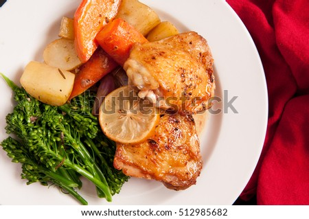 crispy chicken thighs with fingerling potatoes, carrots and green vegetables