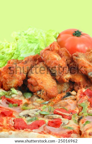 crispy chicken wings and  ham pizza with red and green peppers and salad - stock photo