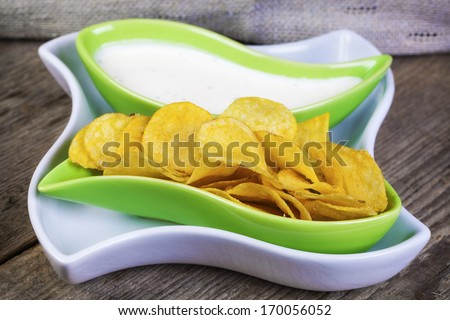 Crispy chips in green bowl on wooden boards - stock photo