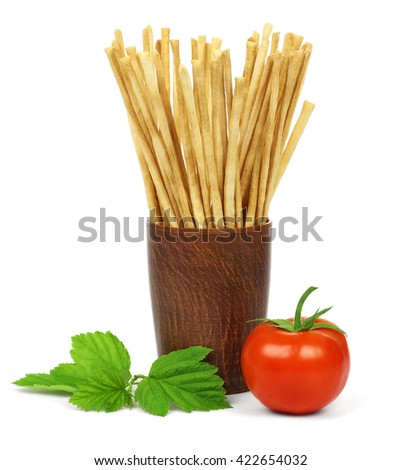 Crispy crunchy long bread sticks in a ceramic cup, a tomato and green leaves, isolated on a white background. - stock photo