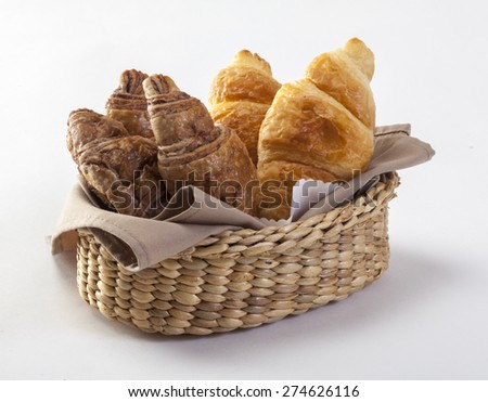 Crispy fresh croissants in a basket isolated on white - stock photo